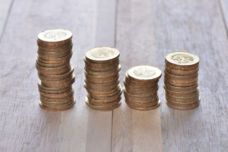 Coins stack in row with label on wooden background, financial concept. Focus on foreground with blur background.