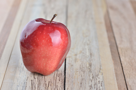 Sweet red apple on wooden background