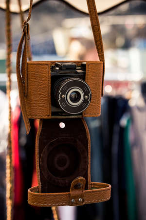 Old vintage analog camera in a light brown leather case.