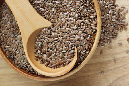 gold flax: Flax seeds on the wooden plate and wooden spoon Stock Photo