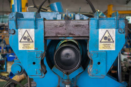 danger signs: Torque machine with Danger Moving Machinery sign.