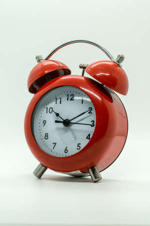 Red vintage alarm clock isolated on white background.