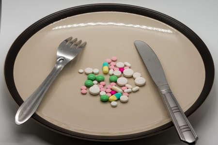 Multiple color drug and pills on ceramic dish with folk and knife. Standard-Bild