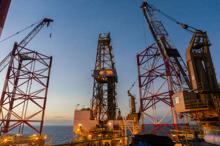 Offshore jackup drilling rigs legs with view of derrick and crane in background.