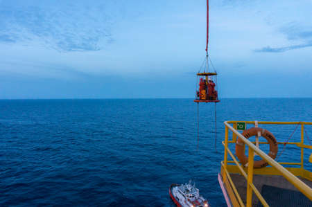 Personal transfer operation to transfer personal with personal transfer basket from offshore jackup drilling rig to crew boat. Stock Photo