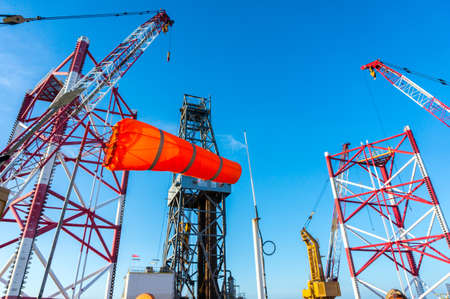 Orange wind sock on offshore jackup drilling rig with view of derrick crane and jackup leg in background. Stock Photo