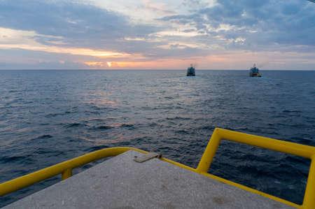Sunrise view from offshore jackup drilling rig, with couple of supply baot.