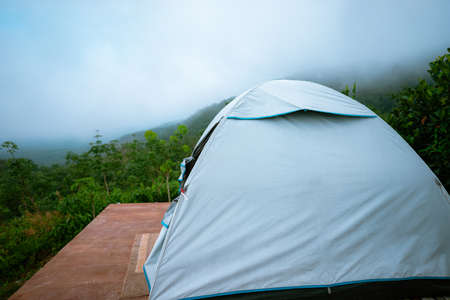 white tent on wooden platform in the middle of the forest with view of mountain, green trees and fog. Standard-Bild