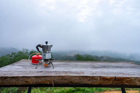 Portable coffee maker on fold-able gas stove with manual coffee grinder on wooden table in the middle of the forest with view of mountain, green trees and cloudy sky.