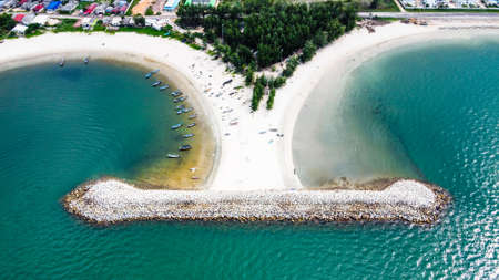 Aerial photo of breakwater the beach with view of group of people and small fishing boat on white sand beach, trees and clear sea water.