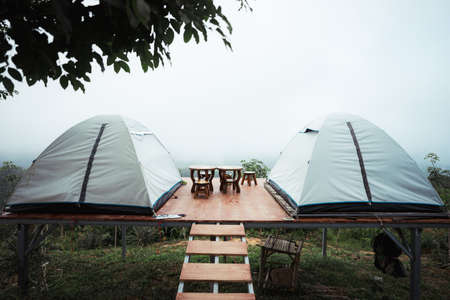 Couple of tent on wooden platform with wooden chairs and table in the middle of the forest with view of mountain, green trees and fog.
