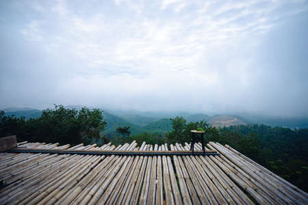 Wooden chair on bamboo platform in the middle of the forest with view of mountain, green trees and fog.