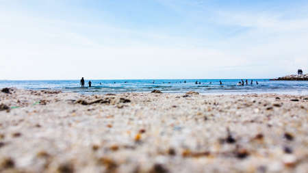 Group of people swimming at the beach with blue sky and close up photo of sand beach.