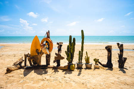 Cactus, wooden block, surf board on the beach with blue sea water, clear blue sky and small white cloud.