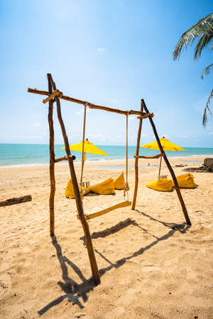 Wooden swing on the beach with yellow umbrella and yellow beach chairs with brown sand, blue sea water, clear blue sky and coconut trees in background.
