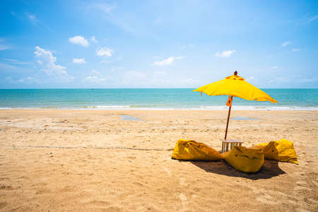 Yellow umbrella with yellow beach chairs on the beach with clear sea water, blue sky and white cloud.