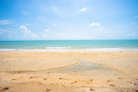 Brown sand beach with clear blue sea water and small wave and blue sky with small white cloud. Standard-Bild