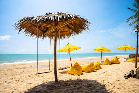 Yellow umbrella with yellow beach chairs on the beach with brown sand, blue sea water, clear blue sky and coconut trees in background. Standard-Bild