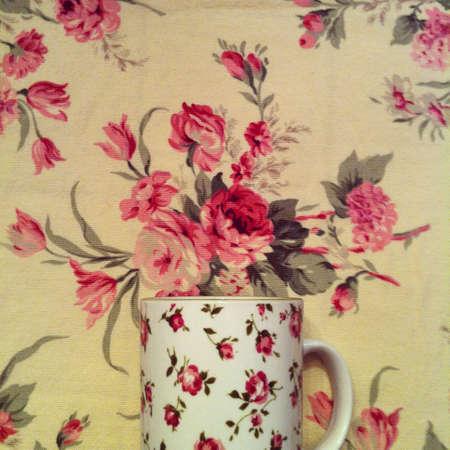 Rosy mug on a rosy table cloth Stock Photo