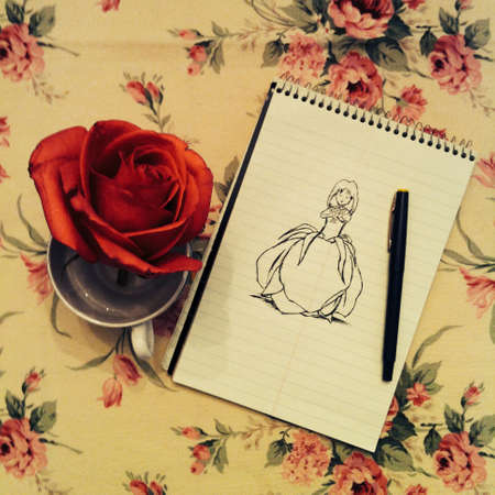 Red rose on a teacup beside sketch in note pad
