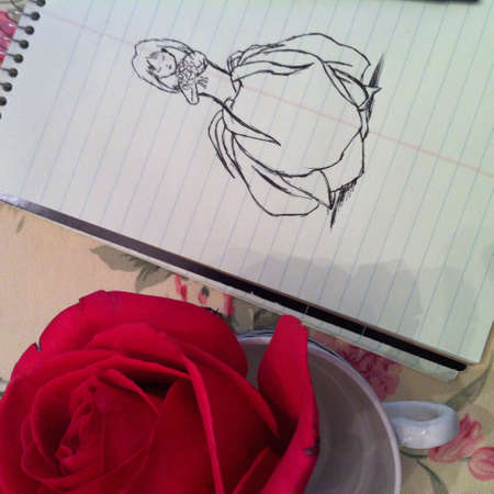 beside: Red rose on a teacup beside sketch in note pad