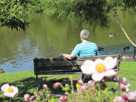 a man is seating on a bench at Elizabeth Park, Hartford