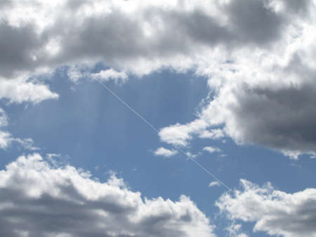 Trace of an airplane against cloudy sky Imagens