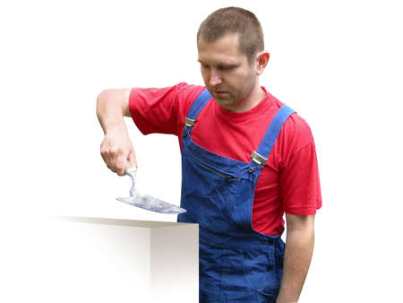 Builder worker in overalls, holding instrument. Isolated on white. Clipping path.  Stock Photo