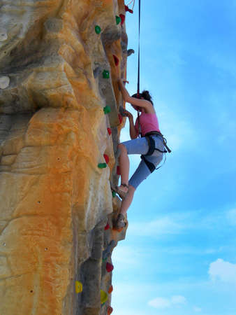 Active alpinist girl climbing artificial rock - sport, recreation