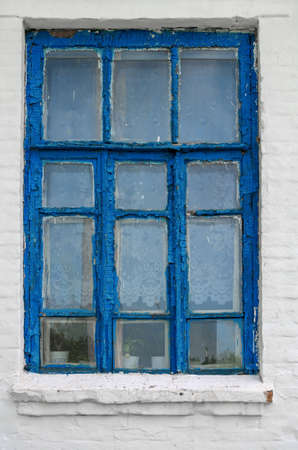 Ancient  window with peeling blue paint on a white wall. Stock Photo