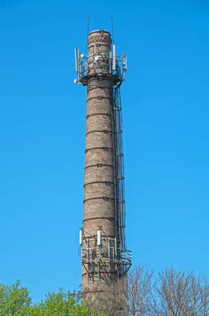 exhaust system: Brick flue with connected repeaters in an industrial area on the sky background Stock Photo