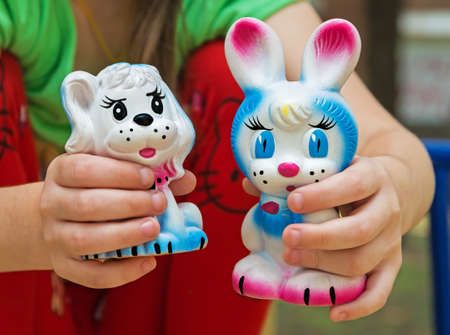 Old rubber toy in form of a colored rabbit and doggy for young children Stock Photo