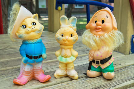 Old rubber toys in form of a colored rabbit, cat and gnome for young children