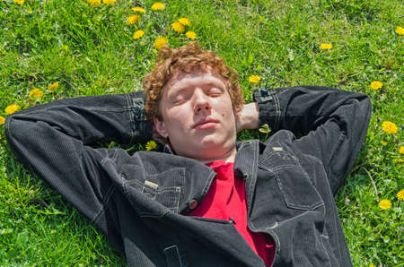 Young guy lying on the field with dandelions eyes closed Фото со стока