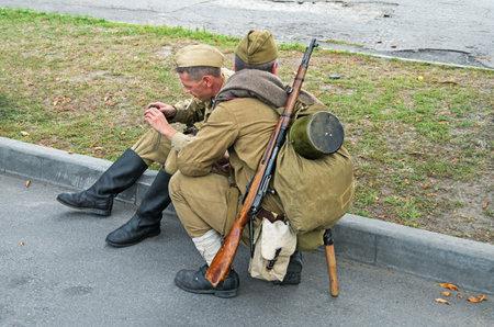 Dnepropetrovsk, Ukraine - September 14, 2013: Group of unidentified re-enactors dressed as Soviet soldiers in greatcoat resting