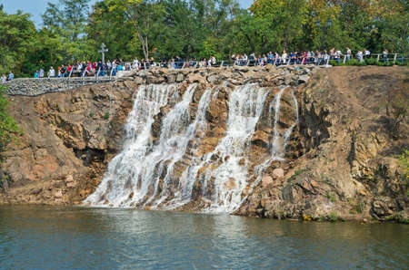 Dnepropetrovsk, Ukraine - September 14, 2013: View of the green river island with waterfall on a clear sunny day