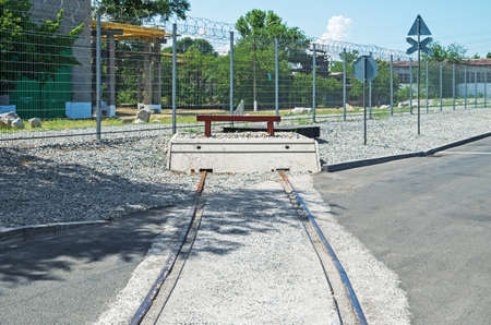 End of rail in an industrial area on against the background of a fence with barbed wire 写真素材