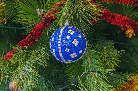 Blue with sparkling silver sparkles Christmas decorationsin the form of a ball hanging on a pine branch