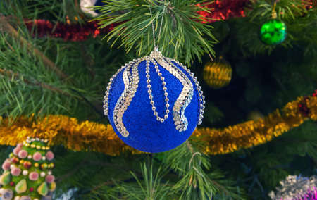 Blue with sparkling silver sequins Christmas decorationsin the form of a ball hanging on a pine branch