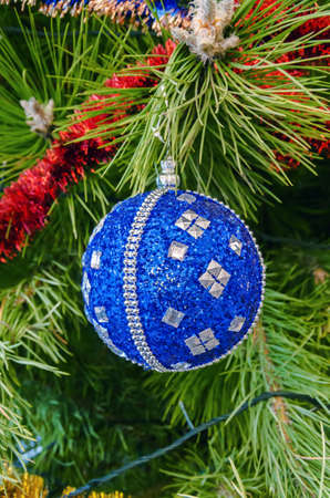 Dark blue with sparkling silver sequins Christmas decorationsin the form of a ball hanging on a pine branch