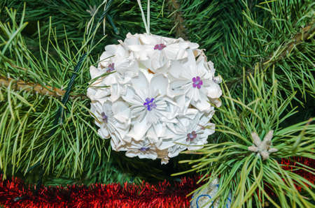 Made of white paper Christmas decorationsin the form of a ball hanging on a pine branch