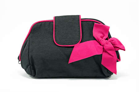 Black bag for cosmetics and accessories to make-up with a pink bow isolated on a white background