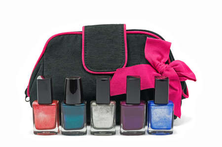 Black bag for cosmetics and accessories with a pink bow and bottles of multicolored nail polish isolated on a white background Banco de Imagens