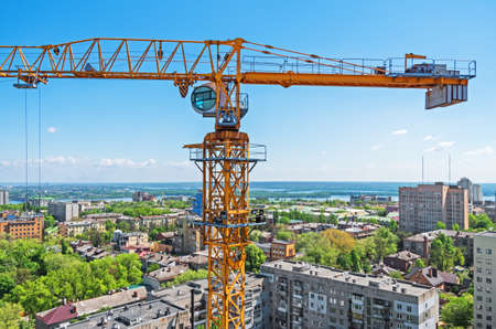 View of crane with a under construction skyscraper on background of the city