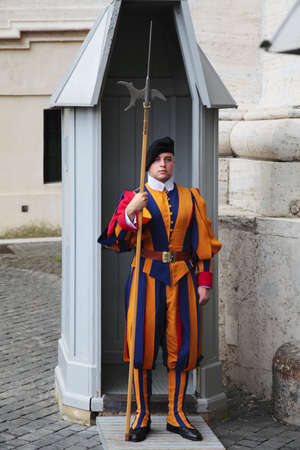 VATICAN CITY, ROME, ITALY - SEPTEMBER 2012: Papal Swiss Guard in their traditional uniform stands guard at the entrance of Saint Peters Basilica on September 5, 2012