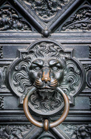 The bronze knocker in the shape of a lion head from the gate of the Cologne Cathedral in Germany photo