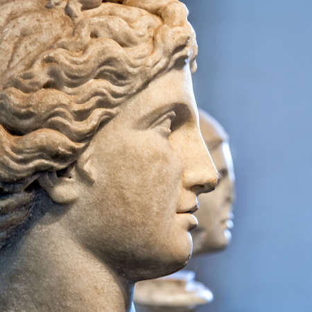 Two ancient marble faces in a profile view