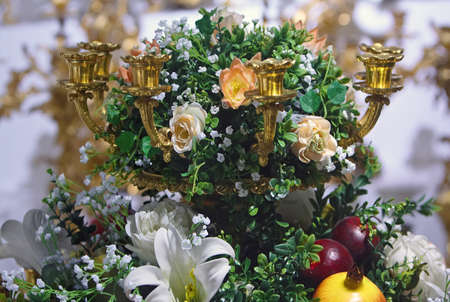 The detail of golden candlestick with flowers photo