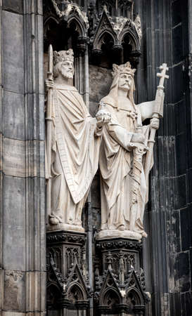 Two medieval gothic statues of kings decorating entry to cathedral in Cologne, Germany Stock Photo