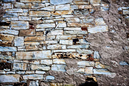 Traditional old stone wall with the rest of the plaster Stock Photo